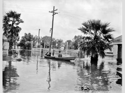 Two people in a row boat in a Flooded New Orleans amusement park.