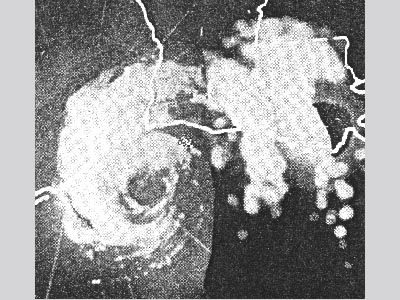 A grainy black and white radar image showing a circular spiral