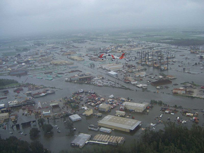 A US Coast Gaurd helicopter flying over a flooded city.